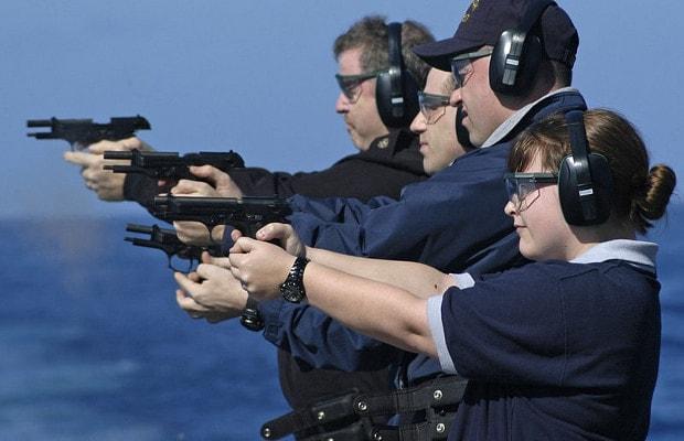 team of people shooting handguns outside