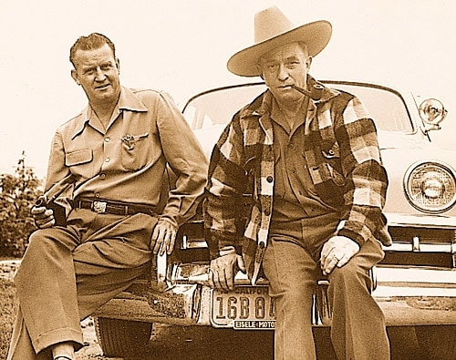 elmer keith sitting on car with one person