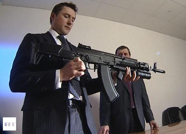 russian in suit presenting ak