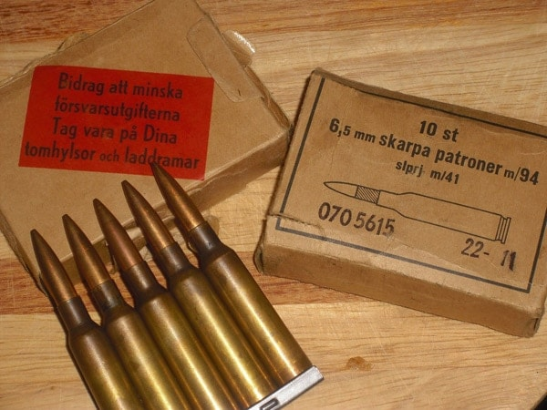 Some 6.5 X 55 mm cartridges sitting on a table.