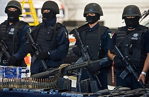 masked authorities with seized guns