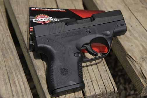 beretta nano pistol on a wood porch on top of ammo
