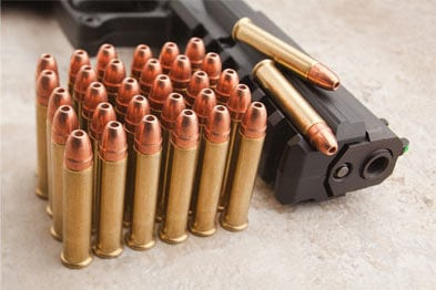 winchester bullets resting on handgun
