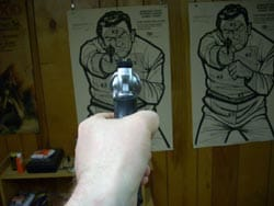 Lone hand holds a revolver and aims it at a paper target.