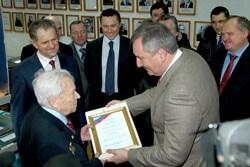 politicians awarding medal to senior citizen