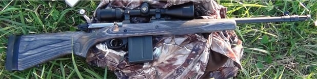 gunsite scout rifle on a camo jacket in the grass
