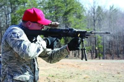 man in hat shooting rifle at outdoor range