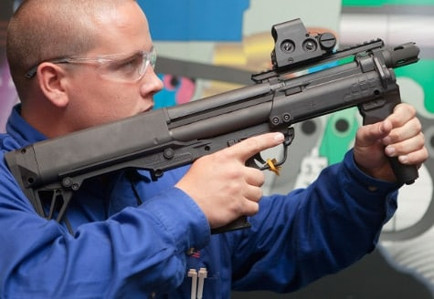 Kel Tec employee shoulders the KSG Shortie and points it into the air.