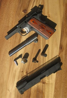 The Springfield Range Officer field stripped and sitting on a table.