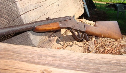 Stevens Maynard .22 LR Rifle leaning against a stack of logs with lawn furniture in the background.