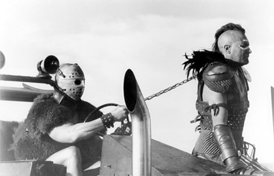 """Humungus and Wez riding around in a dunebuggy in """"Mad Max 2: The Road Warrior"""""""