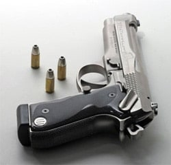 handgun on table with bullet standing up