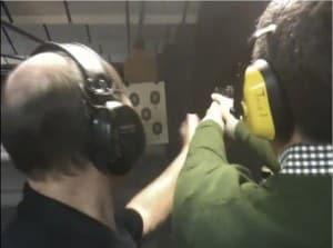 2 men wearing headphones shooting guns at range