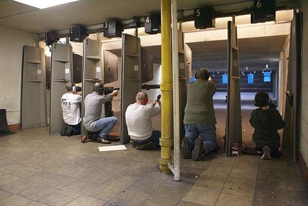 group photo of men shooting runs at inside range