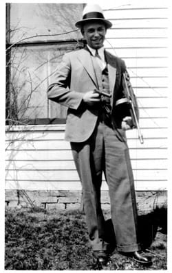 Dillinger posing with his wooden Colt, and a steel Thompson he borrowed from the police.