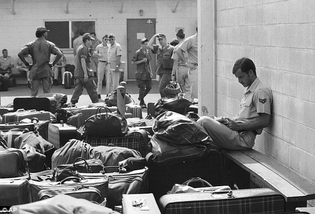 In this March 27, 1973 photo, surrounded by luggage of other departing GIs, U.S. Air Force airman reads paperback novel as he waits to begin processing at Camp Alpha on Saigon's Tan Son Nhut airbase in Saigon as troop withdraw