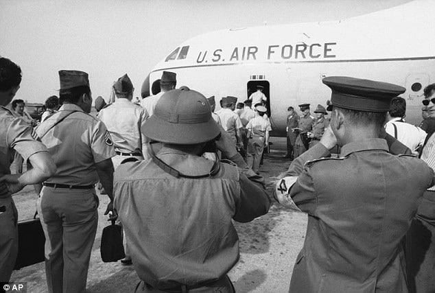 In this March 27, 1973 photo, Viet Cong and North Vietnamese members of the joint military commission, foreground, shoot photos of U.S. troops as they board an Air Force plane for the flight home from Saigon's Tan Son Nhut Air Base