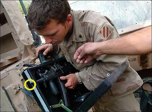 Soldier inspecting firing port inside briefcase