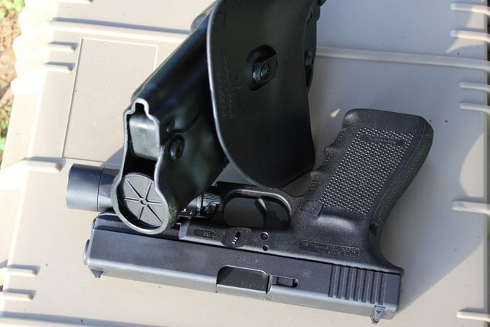 als holster sitting next to gun on case