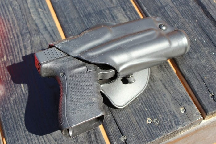 handgun in Safariland ALS Holster sitting on wood table