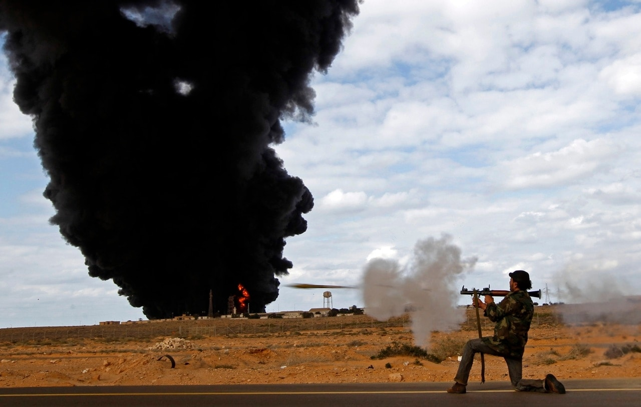 A rebel fighter fires a rocket-propelled grenade launcher in front of a gas storage terminal during a battle on the road between Ras Lanuf and Bin Jiwad