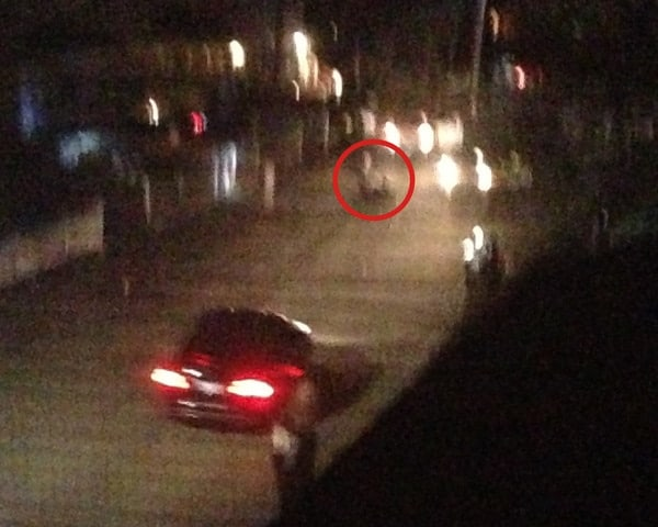 This is a zoom-in from the last image and the red circle highlights where one of the brothers was taken down and still laying in the street. The black SUV proceeded to accelerate towards the officers and drove in between the two cars at the top of the picture. The SUV side swiped both cars taking out doors and windows and ultimately broke through the vehicle barricade and continued driving west on Laurel St. This was the last I saw of the black SUV.