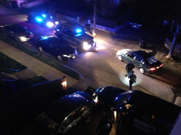 """This image was taken from the east-facing window. As soon as the black SUV had left the street officers rushed toward the green sedan and the spot of the shooting. As soon as officers got to the vehicle they started alerting all others on scene that there were """"IEDs"""" on the street and for everyone examining the scene to clear the entire street. Also pictured at the bottom of the image is a Watertown Police SUV that had crashed in our driveway at the start of the gunfight and had many of its windows shot out. (Taken 12:57:52AM)"""