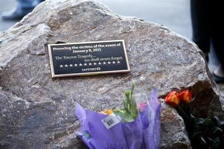 A plaque and flowers for victims of the January 8, 2011 Tucson shooting, are seen during a news conference in Tucson