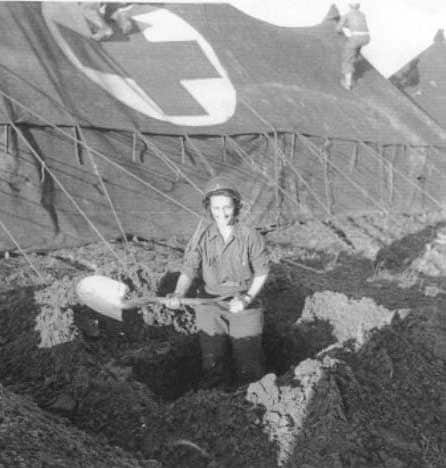 U.S. Army nurse digs in on Anzio beachhead as corpsmen set up hospital tents. (Photo credit: Evelyn Monahan and Rosemary Neidel-Greenlee)