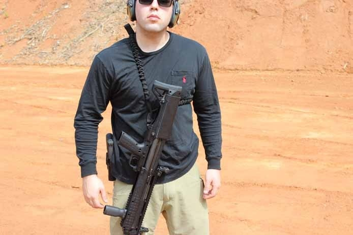 man in tactical gear wearing a ksg in button sling outdoors