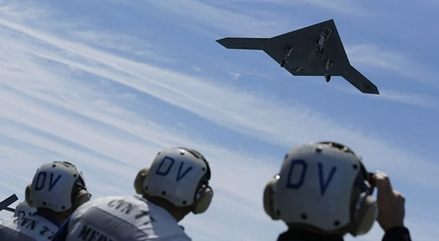 pilots on ground looking up at drone fighter jet