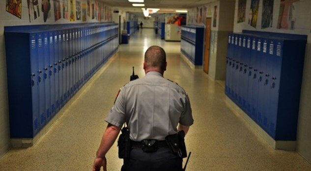 police officer patrolling school hallway with lockers