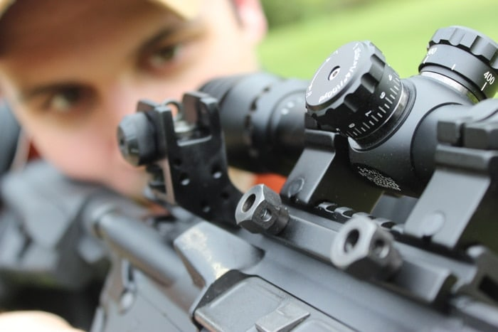 sight focused view of man shooting scoped rifle