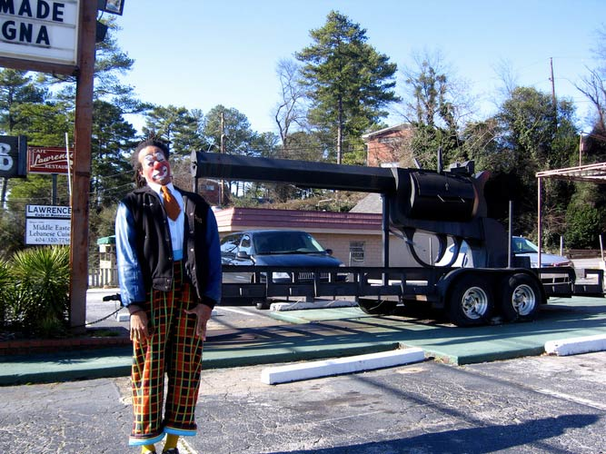 clown next to a trailer with a giant revolver on it