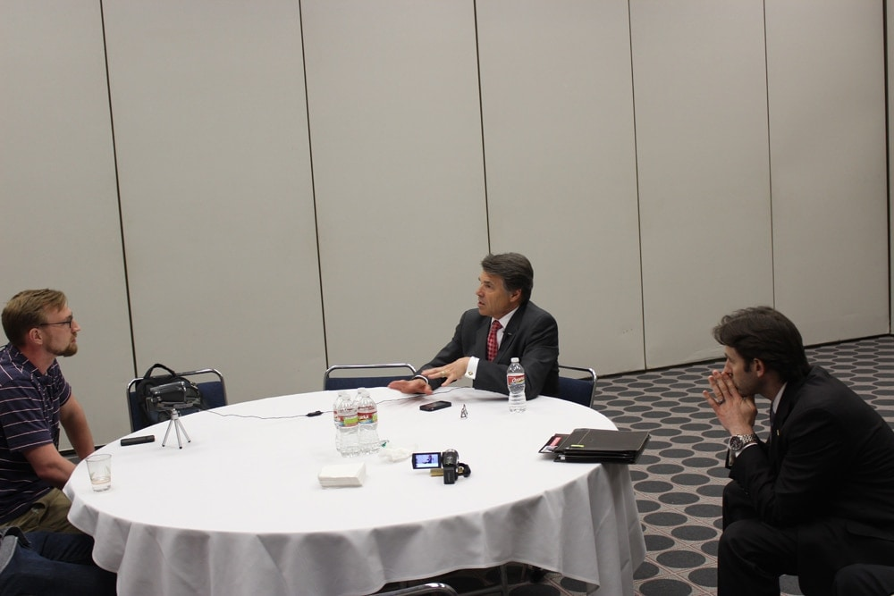 With only a cluttered table between them, Guns.com sits down with Texas Gov. Rick Perry at the NRA annual meeting 2013. (Photo by David Higginbotham)