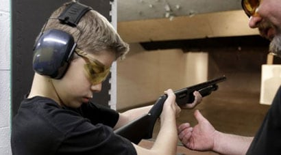 12-year-old Rory Strain is instructed by Dan Blackford on how to properly hold a shotgun. Rory mother, Cheryl, also participated in the program. (Photo credit: AP)