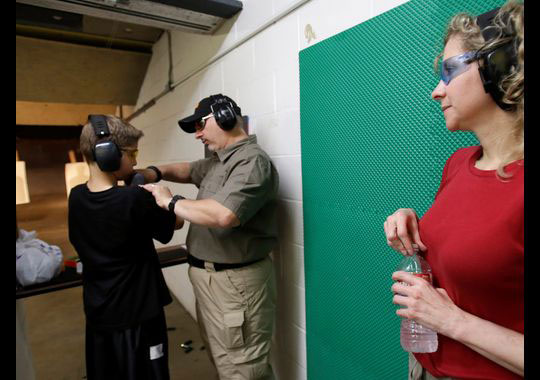 Scott Stevens instructs 12-year-old Rory Strain on how to properly hold a shotgun, as his mother, Cheryl, watches. (Photo credit: AP)