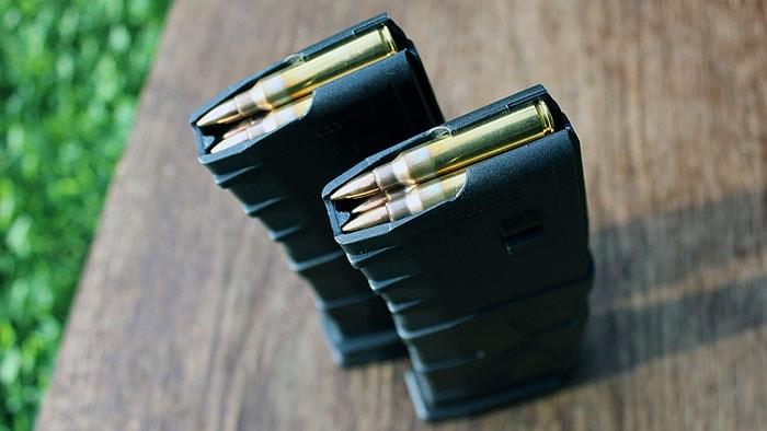 2 loaded magazines sitting on wood table