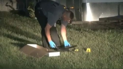 Officers recover a gun dropped when the would-be robbers ran from the homeowner's gunfire. (Photo credit: WKMG, Orlando)
