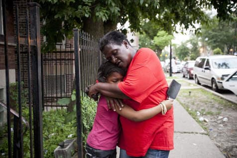 A young girl is comforted near the scene of a gang-related shooting in Chicago this weekend. (Photo credit: Chicago Sun-Times)