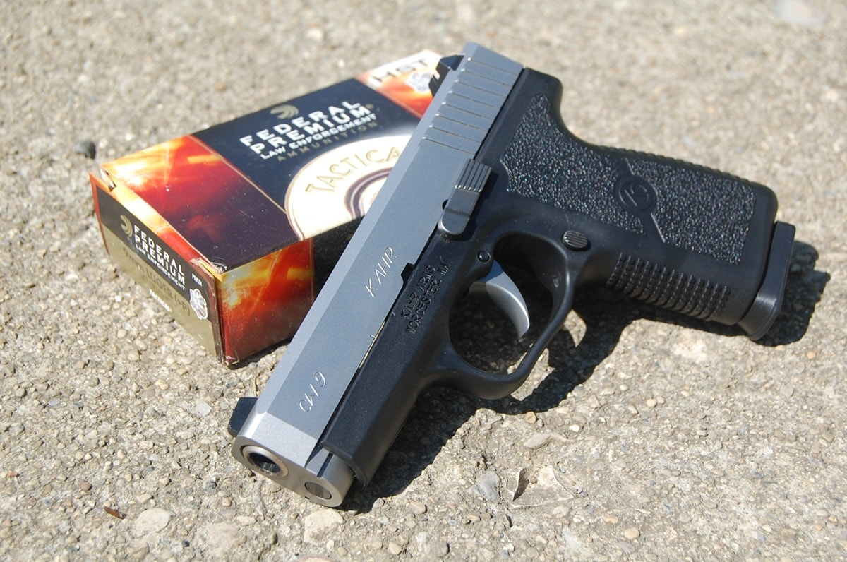 kahr cw9 handgun sitting on top of stone with federal ammo box