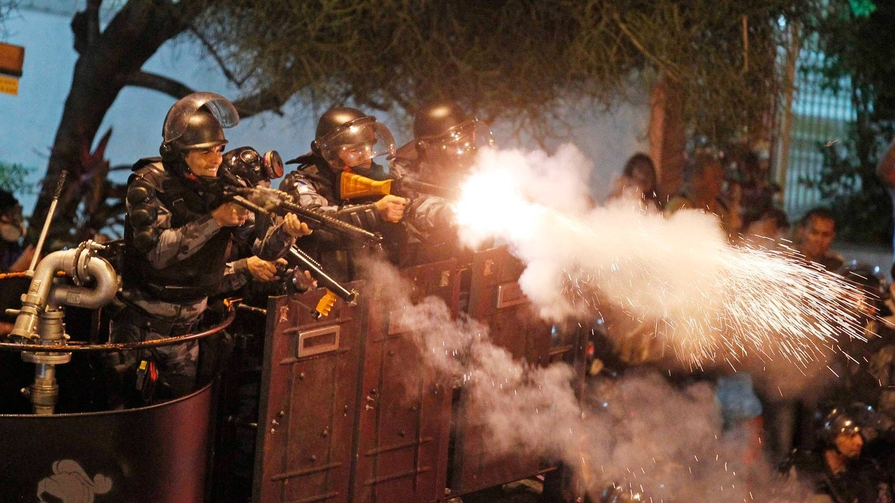 Riot police fire rubber bullets at demonstrator during clashes near Guanabara Palace in Rio de Janeiro