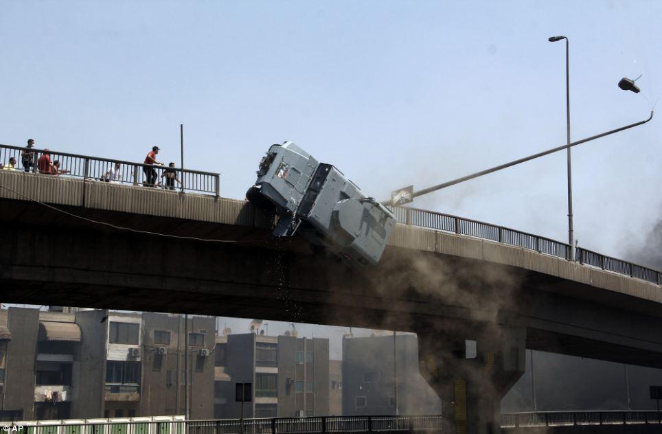 Morsi protestors shoved an armored police van off a 50 ft brdige.