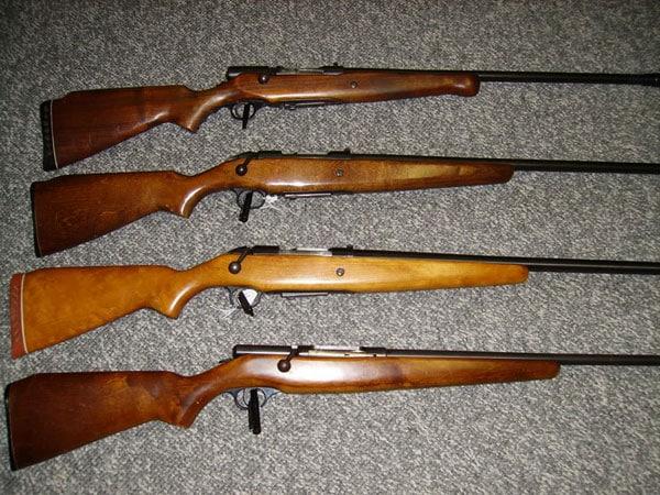 4 mossberg bolt action shotguns displayed on carpet
