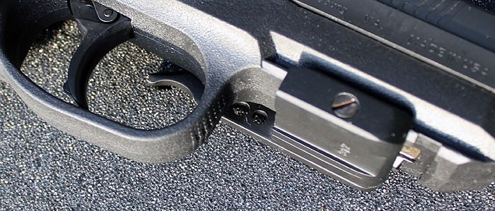 muzzle and trigger view of handgun on blacktop
