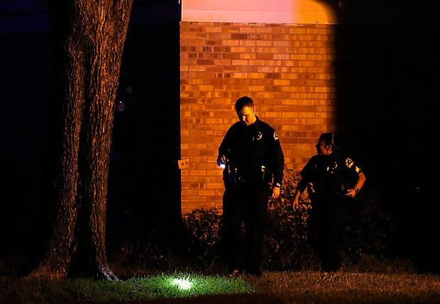 Officers look over the scene during an investigation following the officer involved shooting. (Photo credit: Dallas News)