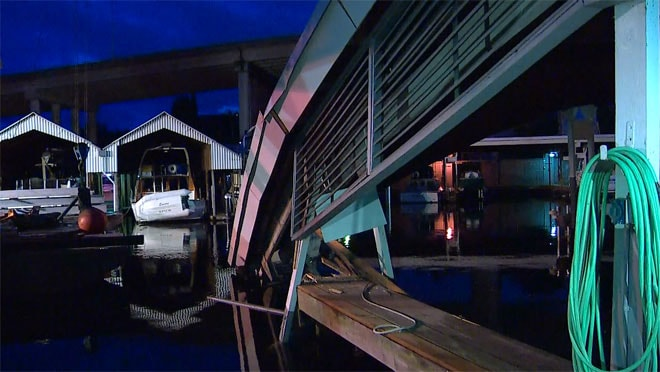 The suspect crashed into a support beam, causing the whole side of the marina roof to fall into the water. (Photo credit: KOMO News)