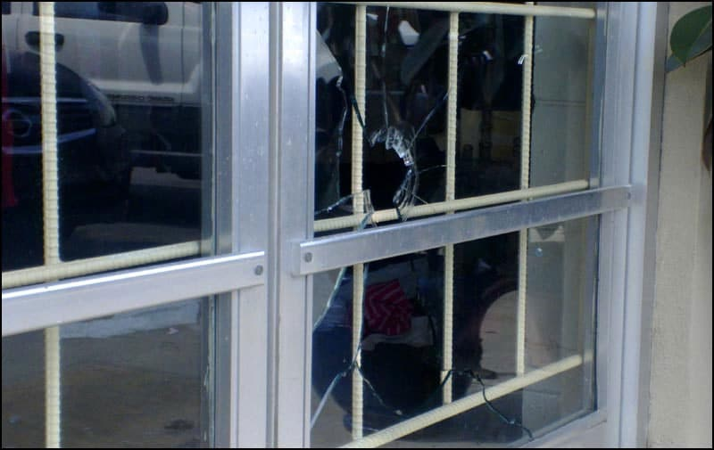 A broken window with a large bullet hole remains from the robbery earlier this week. (Photo credit: WALB)