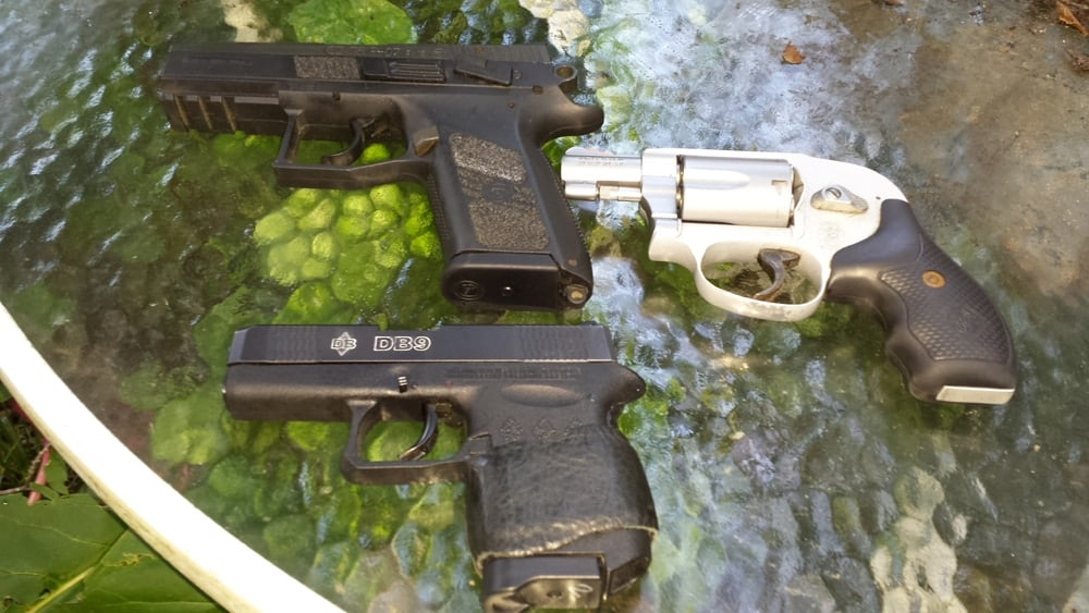 3 pocket pistols sitting on a glass table