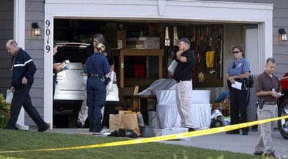 Officers carefully examine the garage where Robison was shot and killed after breaking into a home and attempting to steal a fourth vehicle in a single morning. (Photo credit: KansasCity.com)
